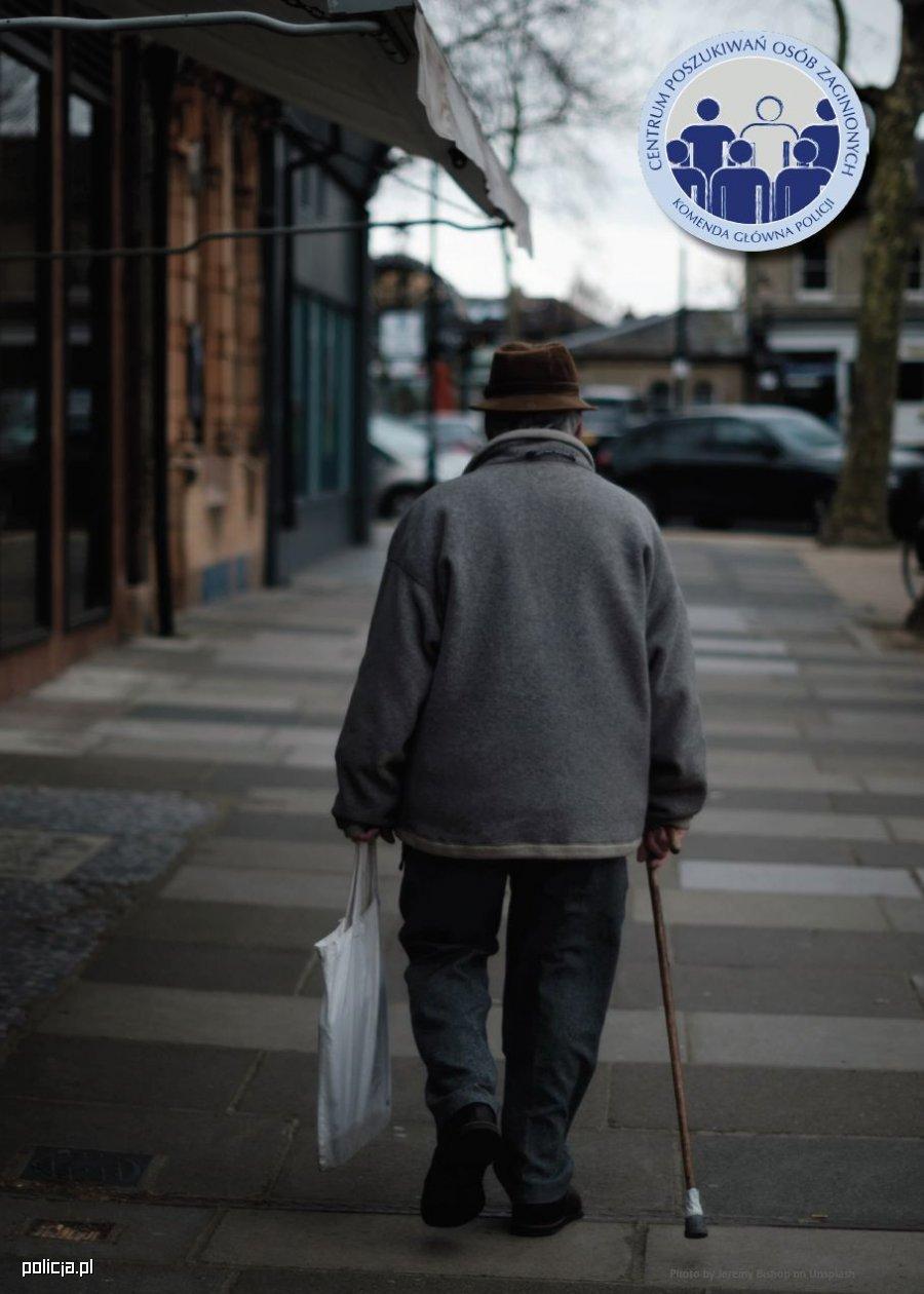 Zdjęcie przedstawia sylwetkę starszego mężczyzny idącego ulicą. W jednej ręce trzyma siatkę z zakupami, w drugiej laskę. Jest odwrócony tyłem. W prawym górnym rogu zdjęcia umieszczone zostało logo Centrum Poszukiwań Osób Zaginionych Komendy Głównej Policji