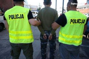 policjanci prowadzą zatrzymanego