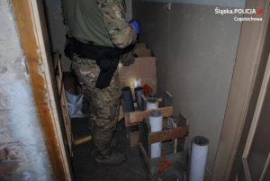 policjant zabezpiecza znalezione materiały wybuchowe