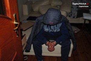 zatrzymany przez policjantów mężczyzna siedzi na łóżku w kurtce z kapturem założonym na głowę