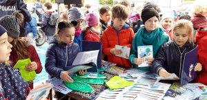 dzieci ze szkoły otrzymują ulotki profilaktyczne podczas pikniku