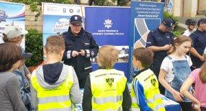 policjantka edukuje dzieci w zakresie bezpieczeństwa nad wodą podczas pikniku