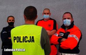 Umundurowana policjantka wraz z dwoma ratownikami medycznymi stoi przodem, tyłem zaś policjant w odblaskowej kamizelce