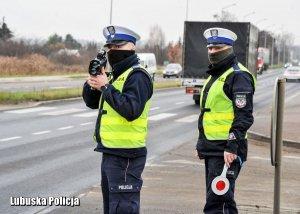 z lewej strony policjant ruchu drogowego trzyma urządzenie do pomiaru prędkości, z prawej strony stoi policjant ruchu drogowego
